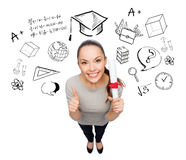 Woman with diploma showing thumbs up over doodles Royalty Free Stock Photo