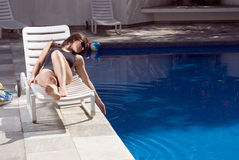 Woman Dipping Hand In Pool - horizontal Stock Photos