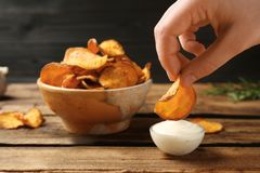 Woman dipping sweet potato chip into sauce on table. Closeup stock photos