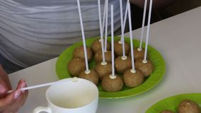A woman dips her stick into melted white chocolate and fixes it in a popcake billet. Blanks are located on the plate. A woman dips her stick into melted white stock video footage