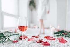 Free Woman Dips Legs Into The Bath, Rose Petal Decor Stock Photography - 119444412