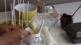 A woman dips a popcake billet into melted white chocolate. Spreads the glaze evenly. Nearby are other ingredients for cooking. A woman dips a popcake billet stock video footage