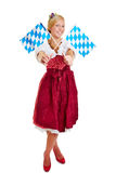 Woman in dirndl with bavarian flags. Happy blonde woman in a dirndl with two bavarian flags stock photo