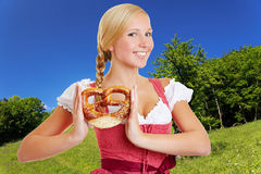 Woman in dirndl in bavarian. Smiling happy woman in dirndl holding a pretzel in a bavarian landscape royalty free stock photography