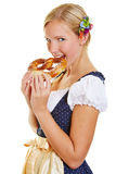 Woman in dirndl biting in a pretzel. Smiling happy woman in a dirndl biting in a delicious pretzel Royalty Free Stock Images