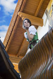 Woman in dirndl blowing a kiss. Woman in dirndl standing on balcony and blowing a kiss stock image
