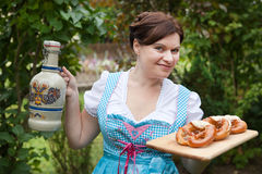 Woman in dirndl dress holding beer and pretzel Stock Image