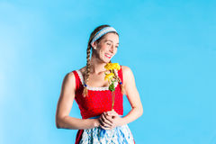 Woman in dirndl dress holding flowers Stock Image