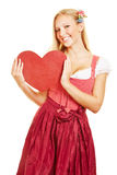Woman in dirndl dress holding red. Smiling young woman in dirndl dress holding a big red heart royalty free stock images