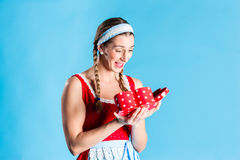 Woman in dirndl dress opening gift Royalty Free Stock Images
