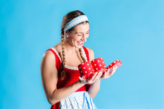 Woman in dirndl dress opening gift - or present stock photo
