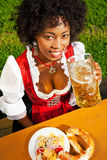 Woman in Dirndl drinking beer Stock Photography
