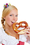 Woman in dirndl eating a pretzel. Young happy woman in a dirndl eating a pretzel stock images