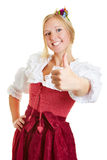 Woman in dirndl holding thumbs up Stock Photo
