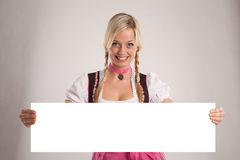 Woman with dirndl holds an empty signboard Stock Image