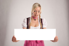 Woman with dirndl holds an empty signboard Stock Photography