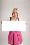 Woman with dirndl holds signboard Royalty Free Stock Image