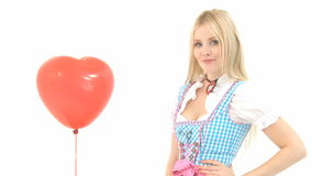 Woman in Dirndl knocks red heart balloon away Stock Image
