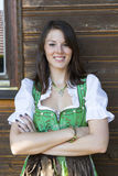Woman in dirndl leaning against a wooden house Stock Photography