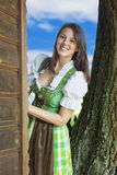 Woman in dirndl looking around the corner. Woman in dirndl standing and looking around the corner royalty free stock photography