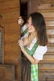 Woman in dirndl looking around the corner. Woman in dirndl standing at a door and looking around the corner royalty free stock photography
