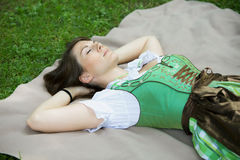 Woman in dirndl lying on blanket outdoors. Young bavarian woman in dirndl lying on blanket in grass stock photos