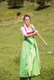 Woman in dirndl in middle age with meadow flower in mouth and ra. Ke on his shoulder goes to work on a mountain meadow stock images