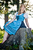 Woman with Dirndl in the Nature. Woman with Dirndl sitting on a Stone stock images
