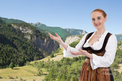 Woman in Dirndl presented Bavaria with background mountains Royalty Free Stock Images