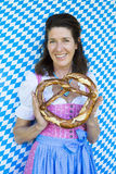 Woman in dirndl with pretzel Stock Photo