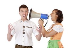 Woman in dirndl screams to man in megaphone royalty free stock photography