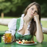 Woman in dirndl sitting at beer garden and looking bored. Young woman in dirndl sitting at beer garden with food and beer and looking bored stock photo