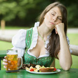 Woman in dirndl sitting in beer garden and sleeps. Young woman in dirndl sleeping at table in beer garden and holding a beer mug royalty free stock image