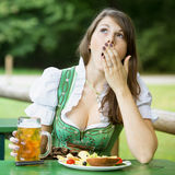 Woman in dirndl sitting at beer garden and is yawning. Young woman in dirndl sitting in beer garden with food and beer and is yawning royalty free stock images