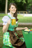 Woman in dirndl sitting in beergarden with beer and food. Young bavarian woman in dirndl sitting outdoors holding a beer mug Royalty Free Stock Images