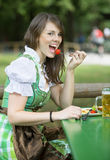 Woman in dirndl sitting outside and eats. Young bavarian woman in dirndl sitting outside with beer mug and eating stock photo