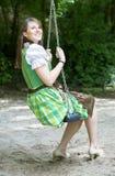 Woman in dirndl sitting on swing. Bavarian woman in dirndl sitting on swing outdoors stock image