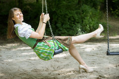Woman in dirndl sitting on swing. Bavarian woman in dirndl sitting on swing outdoors royalty free stock photo