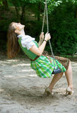 Woman in dirndl sitting on swing. Bavarian woman in dirndl sitting on swing at a playground stock photography