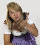 Woman in a dirndl. Smiling blond woman wearing a traditional dress named dirndl while blowing a kiss royalty free stock image