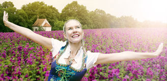 Woman in dirndl spreading her arms in front of purple flower fie. Blond woman in dirndl spreading her arms in front of purple flower field and chapel in the royalty free stock photography