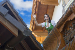 Woman in dirndl standing on balcony. And beckoning to someone royalty free stock photos