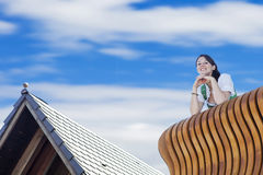 Woman in dirndl standing on balcony. Young woman in dirndl standing on balcony and looking down royalty free stock photography