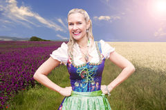 Woman in dirndl standing in front of flower field. Portrait of blonde woman in dirndl standing in front of flower field royalty free stock photography