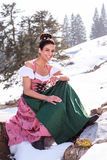 Woman in Dirndl with updo pointing his finger. Woman sitting in Dirndl on a stump in the snow and pointing his finger smiling at the camera royalty free stock photos