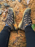 Woman with dirty brown hiking shoes resting on wet muddy area Stock Photo