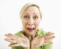Woman with dirty hands. Exasperated adult blonde woman with hands covered in dirt stock image