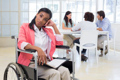 Woman with disability frowning with coworkers are in background Stock Photos