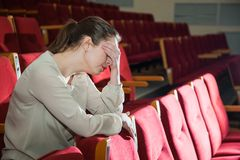 Woman disappointed with show in theater or cinema Royalty Free Stock Photography