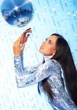 Woman with a disco ball. Brunette woman with a disco ball over abstract background royalty free stock photo